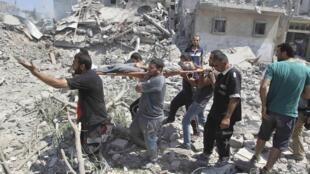Des sauveteurs transportent le corps d'un Palestinien tué dans les bombardements et retrouvés dans les décombres à la faveur de la trêve de ce samedi 26 juillet.