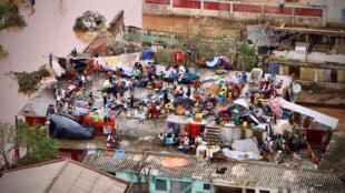 Pessoas reunidas e telhado de uma casa submersa por inundações, em Buzi.
