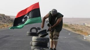 A rebel fighter plants a Kingdom of Libya flag at the last checkpoint before the town of Bani Walid