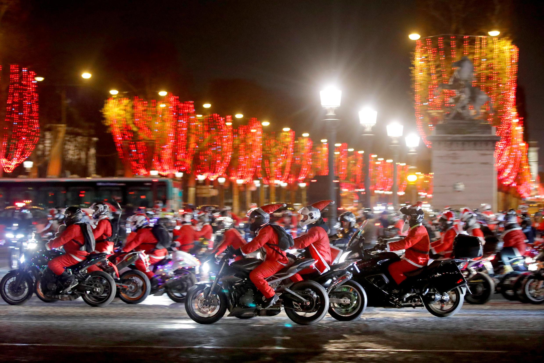 """Đoàn người tham gia """"Carabalade"""" hóa trang thành ông già Noël đi qua đại lộ Champs-Elysées, Paris, ngày 20/12/2018."""