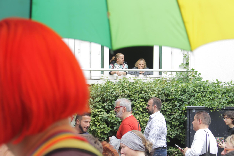 Moradoras assistem à Parada LGBT da janela.