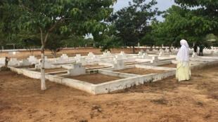 Une famille de l'une des victimes du naufrage du Joola se recueille devant une tombe dans un cimetière de Dakar.