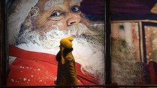 A woman walks past an advertising poster with Santa Claus in central Saint Petersburg on December, 24, 2016.