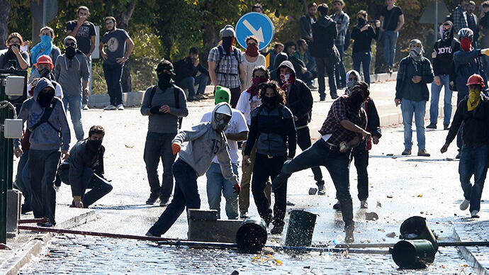 Protesters throw stones as they clash with Turkish riot police during a pro-Kurdish demonstration at the Middle East Technical University in Ankara, 9 October, 2014