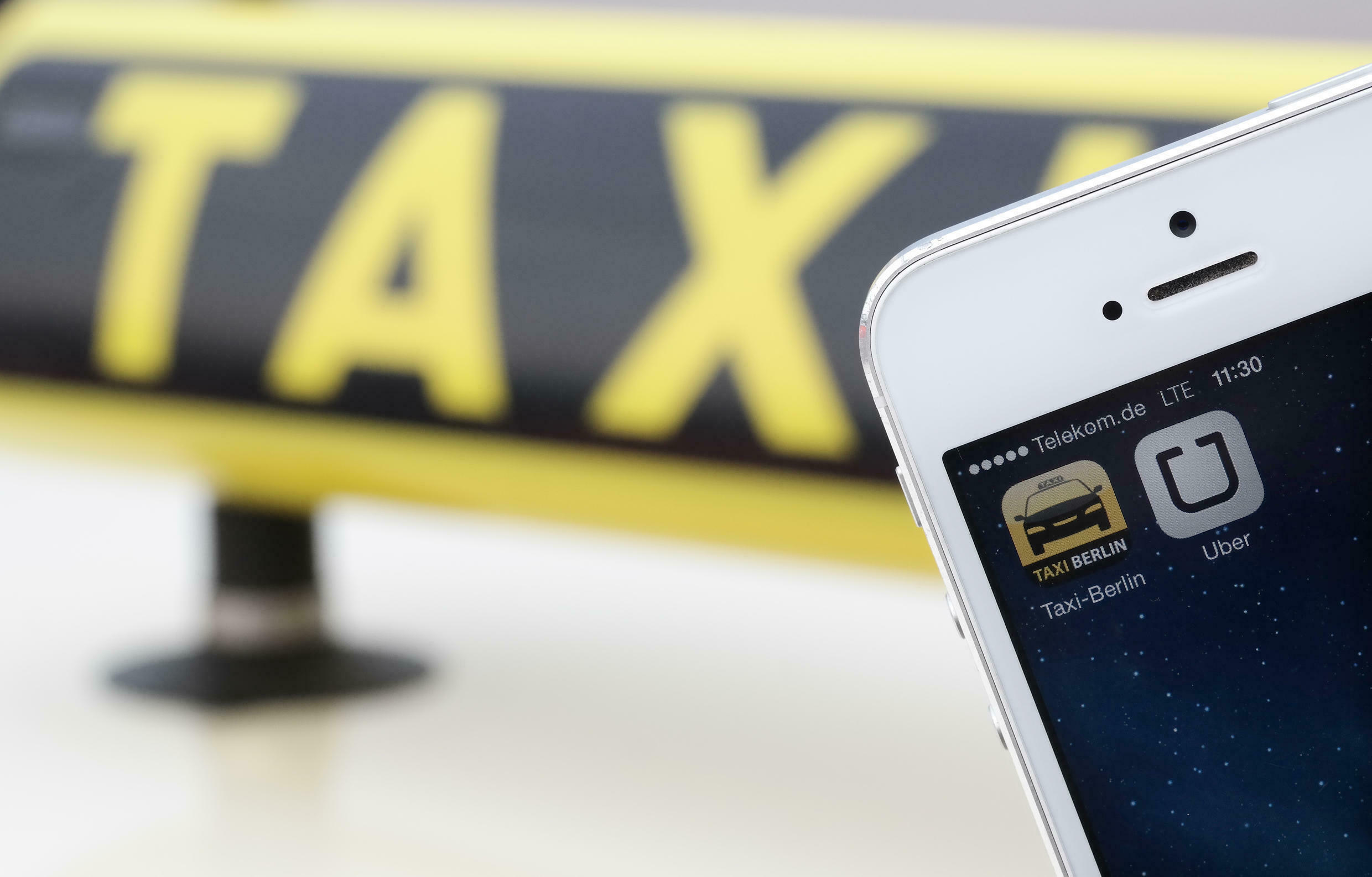 The app 'Uber' on a display of a smartphone in front of a taxi.