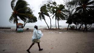 Une femmes se protège du vent et de la pluie alors que l'ouragan Matthew arrive à Les Cayes, en Haïti, le 3 octobre 2016.