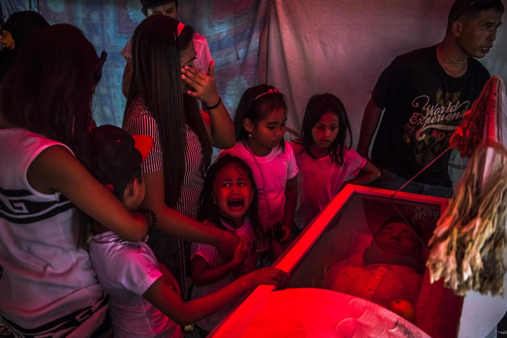 La petite Jimji hurle avant les obsèques de son père. Des traces de torture étaient visibles sur le corps. Selon la police, c'était un dealer ; selon ses proches, il avait voulu suivre une cure de désintoxication. Manille, 10 octobre 2016.