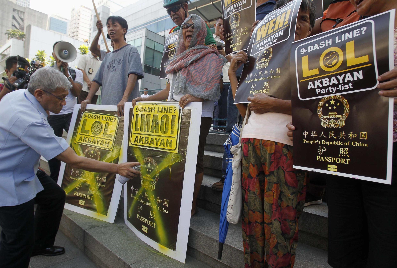 Dân biểu Philippines Walden Bello (trái) tham gia hoạt động biểu tình phản đối hộ chiếu mới có hình lưỡi bò trước lãnh sự quán Trung Quốc tại Makati, Manila ngày 29/11/2012.