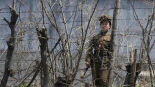 Một nữ quân nhân Bắc Triều Tiên đang canh gác một trại giam bên bờ sông Áp Lục, gần biên giới Bắc Triều Tiên - Trung Quốc ngày 8/5/11.