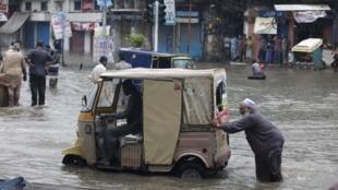 Homem empurra veículo em rua inundada de Lahore, no Paquistão.