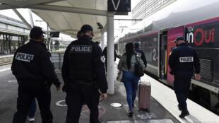 Agentes de la policía francesa detienen a un viajero después de inspeccionar sus documentos en un tren de alta velocidad en Perpiñán, al suroeste de Francia, el 13 de noviembre de 2020