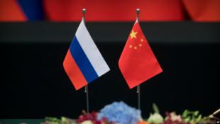 北京人民大會堂舉行簽字儀式上,桌上擺着俄羅斯國旗(左)和中國國旗 2018年6月8日