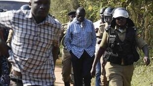 Besigye escorted by police outside his house on the outskirts of Kampala