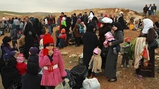 Syrian refugees take a rest after they crossed into Jordanian territory with their families