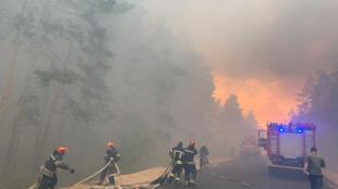 Les pompiers luttent contre un incendie de forêt dans la région de Lougansk, en Ukraine, le 7 juillet 2020.