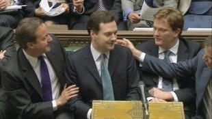 El minsitro de Economía, flanqueado por el primer ministro, David Cameron, y su socio Nick Clegg