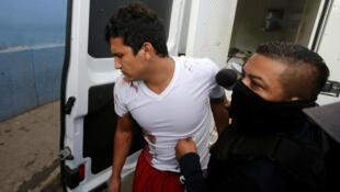 Un policía escolta a un reo herido de la prisión de El Porvenir, a su llegada a un hospital en Tegucigalpa, Honduras. 22 de diciembre de 2019.