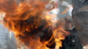 A South Korean veteran holds a torch after burning a North Korean flag during a rally in Seoul