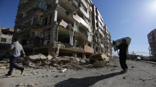 Dos hombres caminan frente a un edificio dañado por el terremoto en Sarpol-e Zahab, Irán, el 13 de noviembre de 2017.