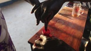 Une femme trempe son doigt dans un bocal d'encre indélébile, après avoir voté lors du référendum sur l'autodétermination d'Abyei, le 28 octobre 2013.