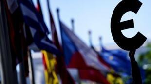 Las banderas de los países de la UE ondean junto a una estatua con el logotipo del euro frente a la sede de la Comisión Europea, el 28 de mayo de 2020 en Bruselas