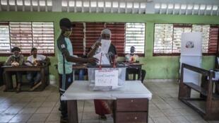 Une femme glisse son bulletin dans l'urne lors de l'élection présidentielle guinéenne à Conakry le 18 septembre 2020 (image d'illustration).