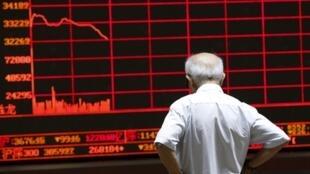 Un investisseur contemple le tableau électronique dans la salle des marchés de Pékin, le 7 juillet 2015.