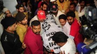 Les équipes médicales évacuent le corps de Zohra Hussein abattue devant sa maison à Karachi, au Pakistan, le 18 mai 2013.