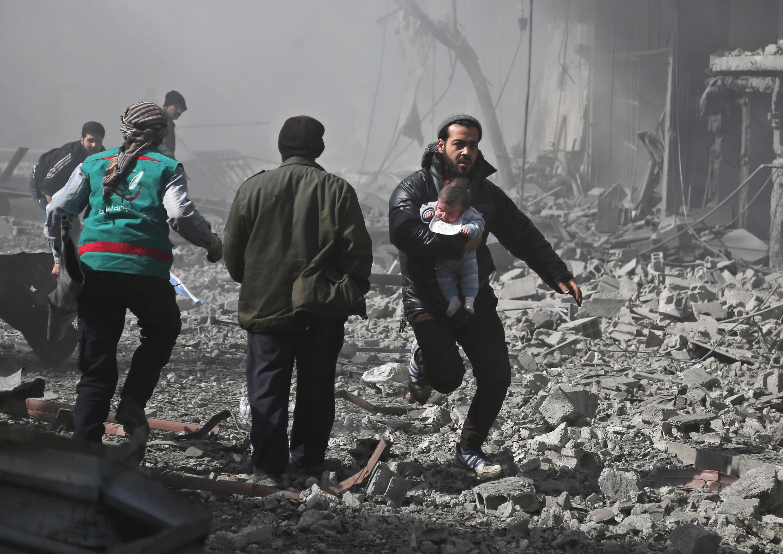 Un enfant dans les bras, un homme fuit les bombardements du régime syrien dans la Ghouta orientale, près de Damas, le 19 février 2018.