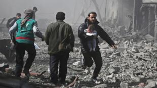 Com uma criança nos braços, um homem foge dos bombardeamentos do regime sírio na Guta Oriental no passado dia 19 de Fevereiro.