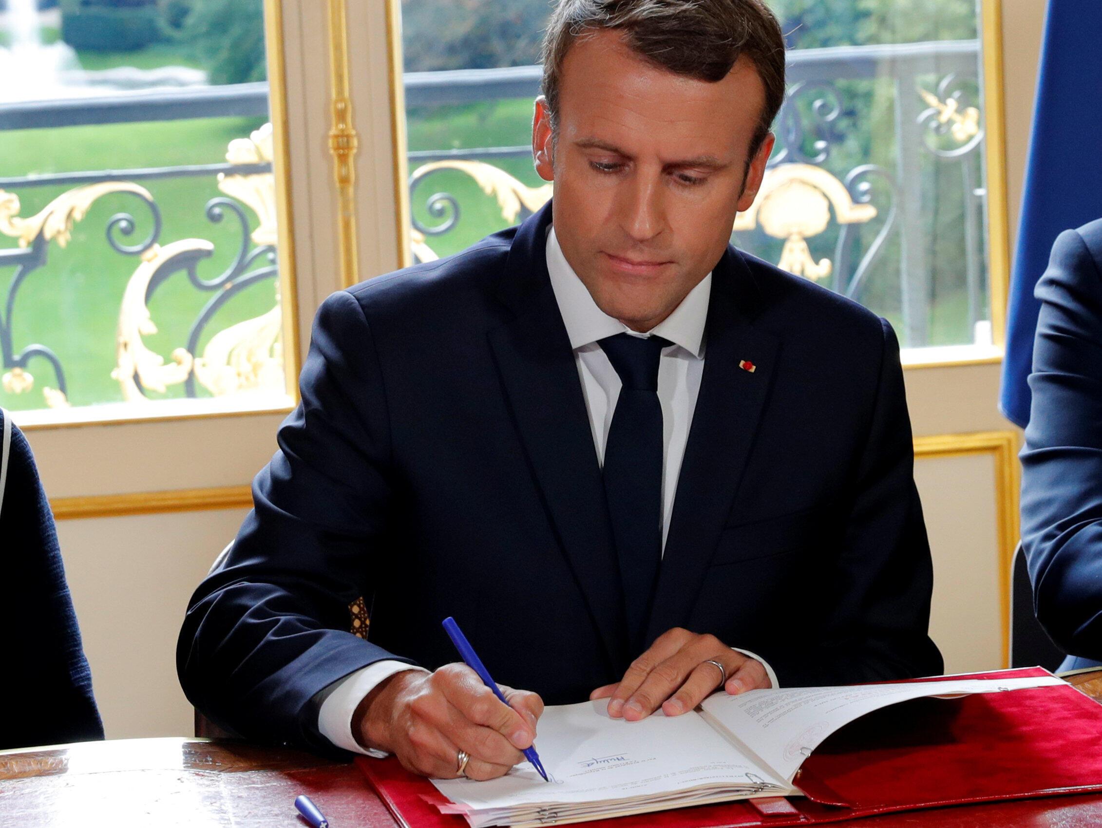 Президент Франции Эмманюэль Макрон подписывает указы о реформе трудового кодекса в своем кабинете в Елисейском дворце, 22 сентября 2017 года, Париж.