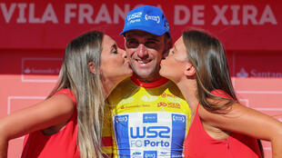 O ciclista espanhol Raúl Alarcón, da W52-FC Porto, festeja no pódio a conquista da camisola amarela.