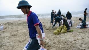 Os habitantes de Da Nang, no Vietnã, usam sacos de plástico para proteger a cidade antes da passagem do supertufão Haiyan.