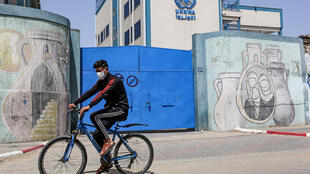 A Palestinian rides a bicycle past the closed gate of a school run by the United Nations Relief and Works Agency for Palestinian Refugees (UNRWA) in the city of Rafah in the Gaza Strip