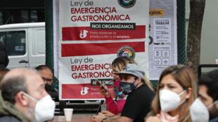 Empleados y clientes participan en un salón al aire libre instalado por dueños de restaurantes como protesta contra las restricciones impuestas por el gobierno del presidente argentino Alberto Fernández por la pandemia del coronavirus COVID-19 en la Plaza Serrano, en Buenos Aires, en junio de 2021.