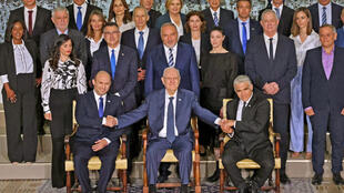Israeli President Reuvin Rivlin (C) flanked by Prime Minister Naftali Bennett (L) and alternate Prime Minister and Foreign Minister Yair Lapid during a photo with the new coalition government, at the President's residence in Jerusalem
