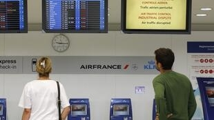 Travellers watch for information updates in French airport as strike goes ahead