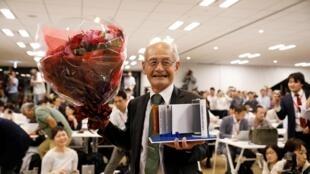 Asahi Kasei Akira Yoshino, prix Nobel de chimie 2019, tient une pile au lithium-ion et un bouquet de fleurs lors d'une conférence de presse à Tokyo, le 9 octobre 2019.