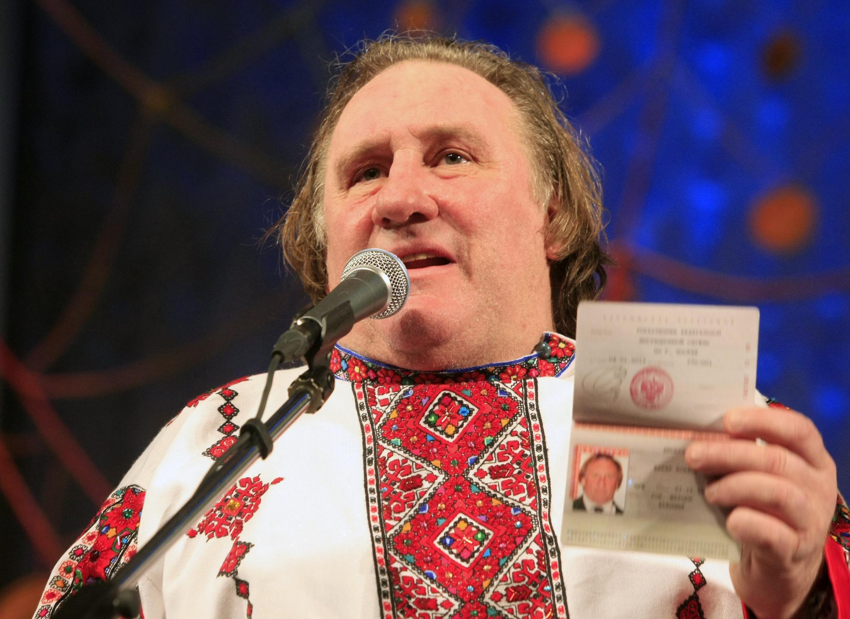 Gérard Depardieu qui a revêtu une tenue traditionnelle de Mordovie montre son passeport russe aux photographes à Saransk, le 6 janvier 2013.