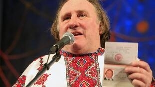 Gérard Depardieu brandishes his Russian passport while dressed in traditional costume of the Mordovia federal republic