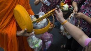 Phật tử cúng dường cho một nhà sư. Ảnh chụp ngày 23/10/2018.