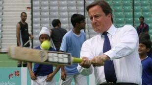 Britain's PM Cameron plays cricket inside a stadium in New Delhi