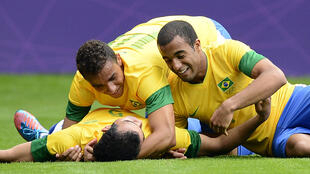 O atacante brasileiro Sandro (deitado) comemora gol com os colegas Danilo (e) e Lucas (d) durante a partida contra a Nova Zelândia nesta quarta-feira.