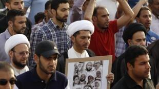 Ali Salman, dirigerant du Wifaq, principal parti d'opposition, brandit une pancarte représentant plusieurs prisonniers politiques à Bahrein, lors de la manifestation organisée par son mouvement le 12 avril 2013.