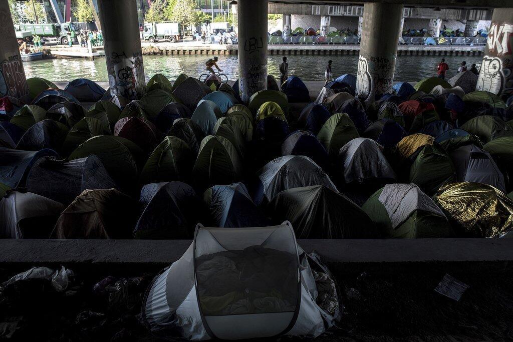 Migrants stand by tents at a makeshift camp set under a bridge near Porte de la Villette, northern Paris on 20 April 2018.