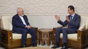 Le président syrien Bachar el-Assad (d) et le ministre des Affaires étrangères Mohammad Javad Zarif, lors de leur entretien, lundi 3 septembre 2018, à Damas.