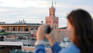 Une touriste prend en photo la place Djemaa el-Fna à Marrakech (Maroc).