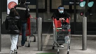 A woman wearing a protective face mask pushes a trolley as she exits from a supermarket in Bordeaux, France.