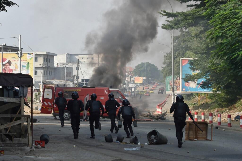 La police anti-émeutes intervient pour disperser des manifestants brûlant des barricades à Abidjan, le 13 août 2020.