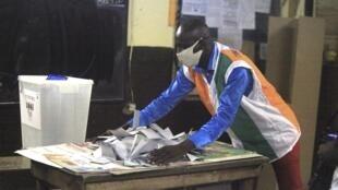 Un agent électoral compte les votes dans un bureau d'Abidjan, le 31 octobre 2020.